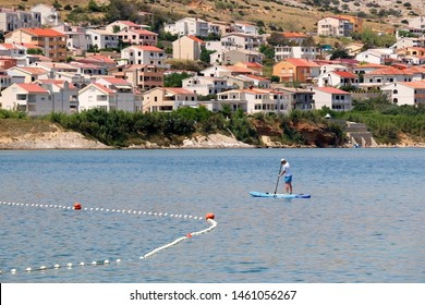 Pag, Croatia - July 7, 2019: Tourist using Stand Up Paddleboard on beach Prosika in town Pag, on island Pag, Croatia.