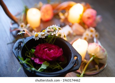 """A pagan altar set for the Mid-Spring Holiday: Beltane.  The altar features deer antler, candles, pastel ribbons, chamomile and Ranunculus blooms, and the message """"Beltane Blessings."""""""