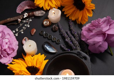 """A pagan or Wiccan altar space decorated for the Summer Solstice, also known as """"Litha.""""  The altar includes sunflowers, roses, lavender, sea shells, candles, a wand, and cauldron."""