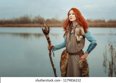 Pagan woman is a shaman, in her hands a sorcerer's staff for performing rituals.