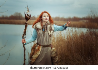 Pagan woman is a shaman with a staff in her hands.