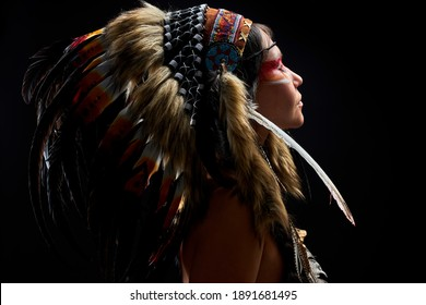 pagan woman is a shaman in studio on black background, side view on female with feathers on hair doing ritual