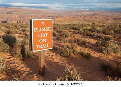 """Page, AZ, USA – October 25, 2016: A sign saying """"please stay on trail"""" at Horseshoe Bend parking lot asking tourists and visitors to stay on trail on their way to Horseshoe Bend viewpoint"""