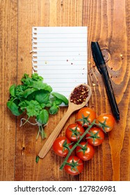 Page of white blank lined paper torn from a ringbound notebook on a wooden table with fresh herbs, tomatoes and peppercorns in a wooden spoon with a pen to write your recipe, menu or grocery list