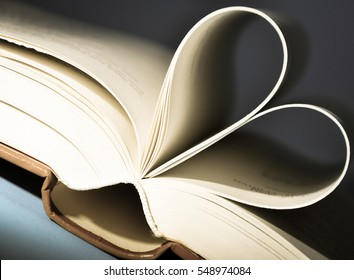 Pages of a book curved into a heart in front of dark background