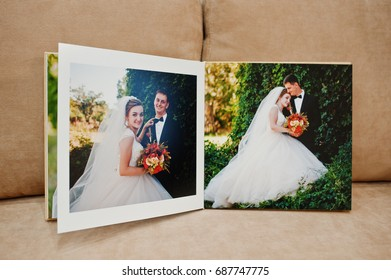 Pages of wedding photobook or wedding album on the sofa with cushions.