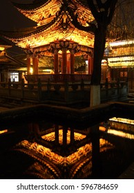 A pagoda is lit at night in Dali, China with the traditional structure reflected in small pond.
