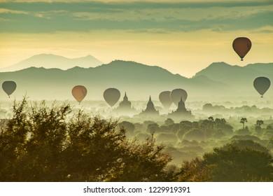 Pagodas and Hot-Air Balloons at misty Old Bagan, Myanmar