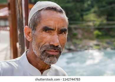 Pahalgam,17,June,2008: Close up portrait of unidentified  muslim man  wearing  embroidered white cap outdoor    staring curiously with river water in background ,Jammu and Kashmir,India,Asia