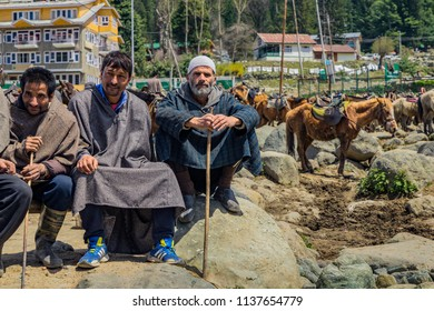 Pahalgam,April,14,2016: Jammu and Kashmir,group  of three  local horsemen posing  in traditional  winter ware with their horses resting in background,   Jammu and Kashmir,India,Asia