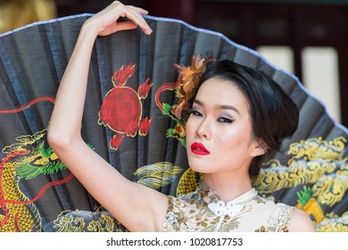 Pahang, Malaysia - 8th February 2018 : A portrait of chinese girl wear Qipao, a chinese style cheongsam and holding a hand fan in conjunction of Chinese New Year festival - illustrative editorial.