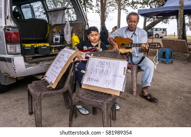 Pahang, Malaysia - February 2017 : Cute young boy and his grandfather playing guitar and singing as street performer at the parking lot.