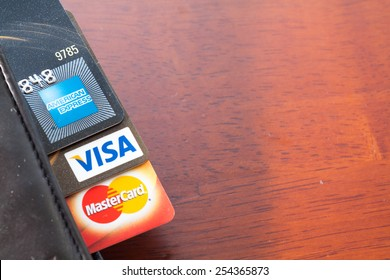 PAHANG , MALAYSIA - FEBRUARY 21, 2015 - Illustrative Editorial,close up of credit cards , master card, VISA and american express in the leather wallet with wood background, product shot