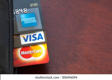 PAHANG , MALAYSIA - JULY 28, 2015 - Illustrative Editorial,close up of credit cards , master card, VISA and american express in the leather wallet with wood background, product shot