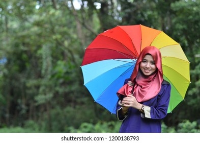 PAHANG, MALAYSIA – MARCH 25, 2012 : The female wearing religious muslim outfit represents individualism, feminism and ethnic and racial acceptance with colorful umbrella. Outdoor photo-shoot.