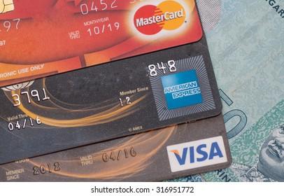 PAHANG , MALAYSIA - SEPTEMBER 15, 2015 - Illustrative Editorial,close up of credit cards , master card, visa and american express on ringgit bank note background, product shot