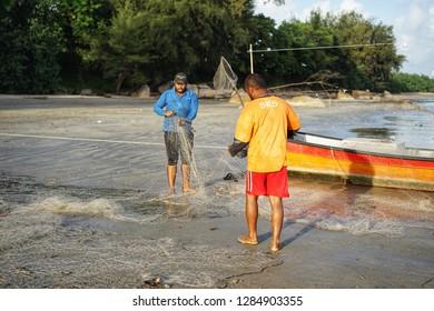PAHANG,MALAYSIA. 11 jan 2019 - two fisherman at beach checking long trawl nets before catching fish at sea