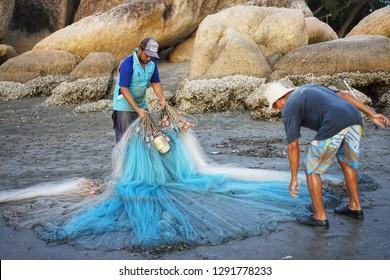 PAHANG,MALAYSIA 11/01/2019 - two fisherman at beach checking long trawl nets before catching fish at sea