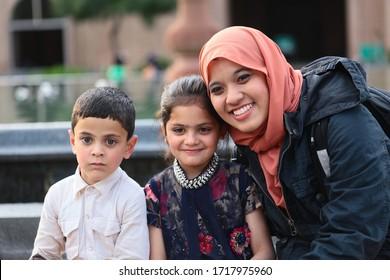 PAHARGAM, SRINAGAR, INDIA - 16 APRIL 2018 : Unidentified tourist woman taking photo with local kids at the Srinagar's Jamia Mosque  at Srinagar City