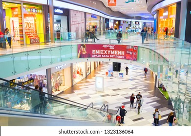 PAHOS, CYPRUS - FEBRUARY 14, 2019: People in shopping center, modern interior design of Kings Avenue Mall with escalator among floors