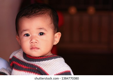 Pai, Mae Hong Son, Thailand- On January 13, 2012. Cute Asian baby wearing white  sweater with dark blue and red strip, black pupils and hairs, Asian traits. Portrait picture