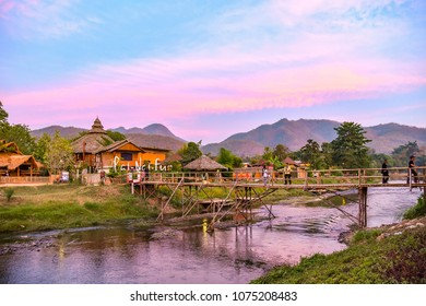 Pai / Thailand - 11 January 2016: Bridge over the Pai river, village and mountains