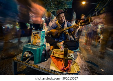PAI, THAILAND - DEC 1, 2013: Blind man plays multiple instruments for donations on street at night market.
