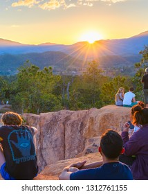 PAI, THAILAND - JAN 7, 2017: People sitting on rocks watching scenic sunset over mountains valley, Pai, Thailand