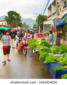 PAI, THAILAND - JANUARY 10, 2017: Women selling greenery at crowded Pai street market, mountains in background, Thailand