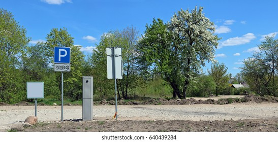 The paid parking is equipped near the village. There is no asphalt, only clay crushed stone and the earth. On a background spring the blossoming apple tree and the solar blue sky.