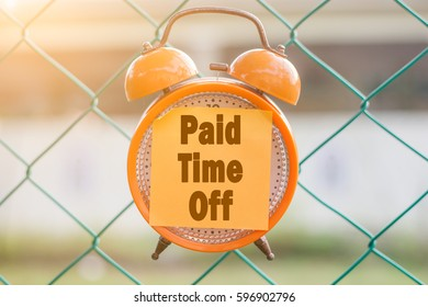 PAID TIME OFF word written on sticky note on orange analog clock hanging on the fence over blurry background