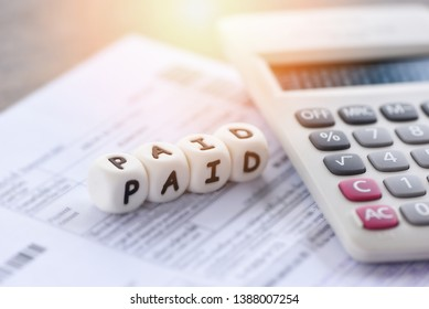 Paid words and calculator on invoice bill paper for time paid payment at office business finances