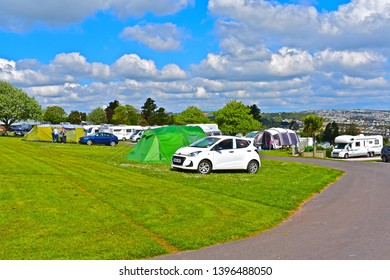 Paignton, Devon / England - 5/4/2019: Campers enjoying fine weather at the Beverley Park Campsite with wonderful views across Torbay towards Torquay. Tents & cars on grass pitches.