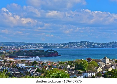 Paignton, Devon / England - 5/4/2019: Panoramic views across Torbay from Goodrington in the foreground to Torquay in the distance. Smoke & steam from Dartmouth Steam Railway as it leaves Goodrington.