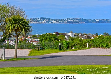 Paignton, Devon / England - 5/6/2019: Stunning sea views from Beverley Park campsite near Goodrington, looking across Torbay towards Torquay. Hardstanding empty pitch with palm tree in foreground.