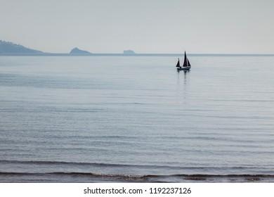 Paignton, Devon, UK - A sailing boat in Torbay on a soft light day.