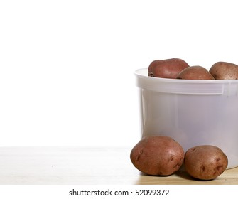 A pail of fresh organic garden red potatoes, shot on a wooden table with a solid white background