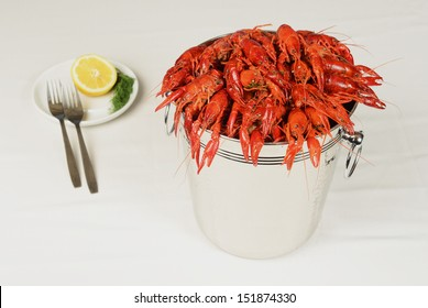 pail full of river lobster served on table with lemon
