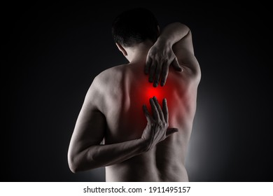 Pain between the shoulder blades, man suffering from backache on black background, painful area highlighted in red