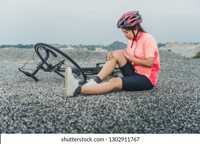 Pain bike injury. Woman with knee joints after biking on bicycle. Girl sitting down with a painful face expression. Mixed race sport fitness model outdoors