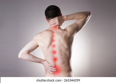 Pain in a body of the man on gray background. Red dot