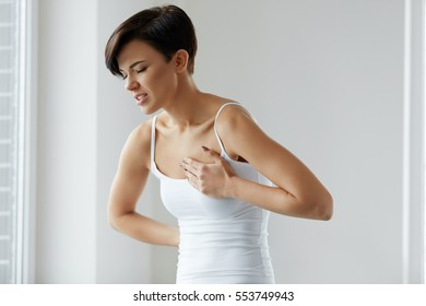 Pain In Chest. Woman Suffering From Painful Feeling In Body. Portrait Of Beautiful Female Having Heart Attack, Holding Hand On Her Chest. Health Problem And Healthcare Concept. High Resolution Image