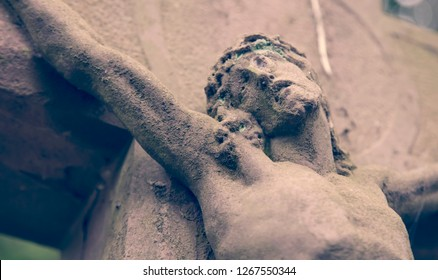 Pain and crucifixion of Jesus Christ as a symbol of resurrection and immortality of the human soul (ancient stone statue)