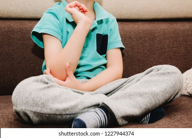 Pain in the elbow, hands of a small child. The little boy is holding his elbow, sitting on the bed. Health problems at the hands of a small child. Suffering and pain in a child.