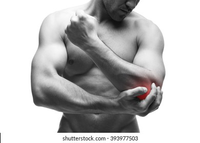 Pain in the elbow. Muscular male body. Handsome bodybuilder posing in studio. Isolated on white background with red dot. Black and white photography