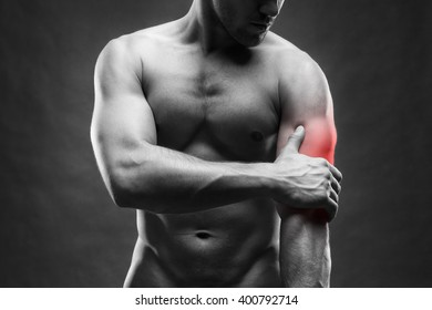 Pain in the elbow. Muscular male body. Handsome bodybuilder posing on gray background. Black and white photo with red dot