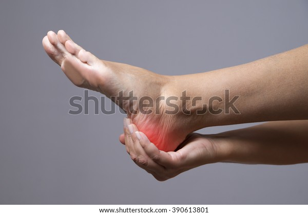 Pain in the foot. Massage of female feet. Ache in the human body on a gray background with red dot