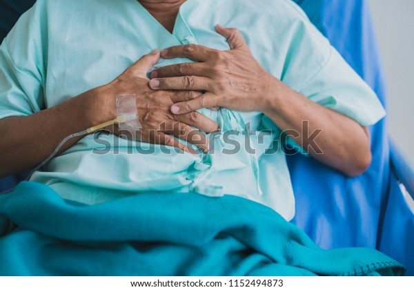 pain and heartburn old senior asian grandfather in patient uniform suffer from body problem  health ideas concept