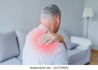 Pain in his shoulder. Upper arm pain, People with body-muscles problem, Healthcare And Medicine concept. Attractive mature man sitting on the bed and holding painful shoulder with another hand.