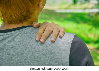 Pain in the human body. Close up of Man with shoulder pain or neck pain. a sports injury. rear view and nature background.